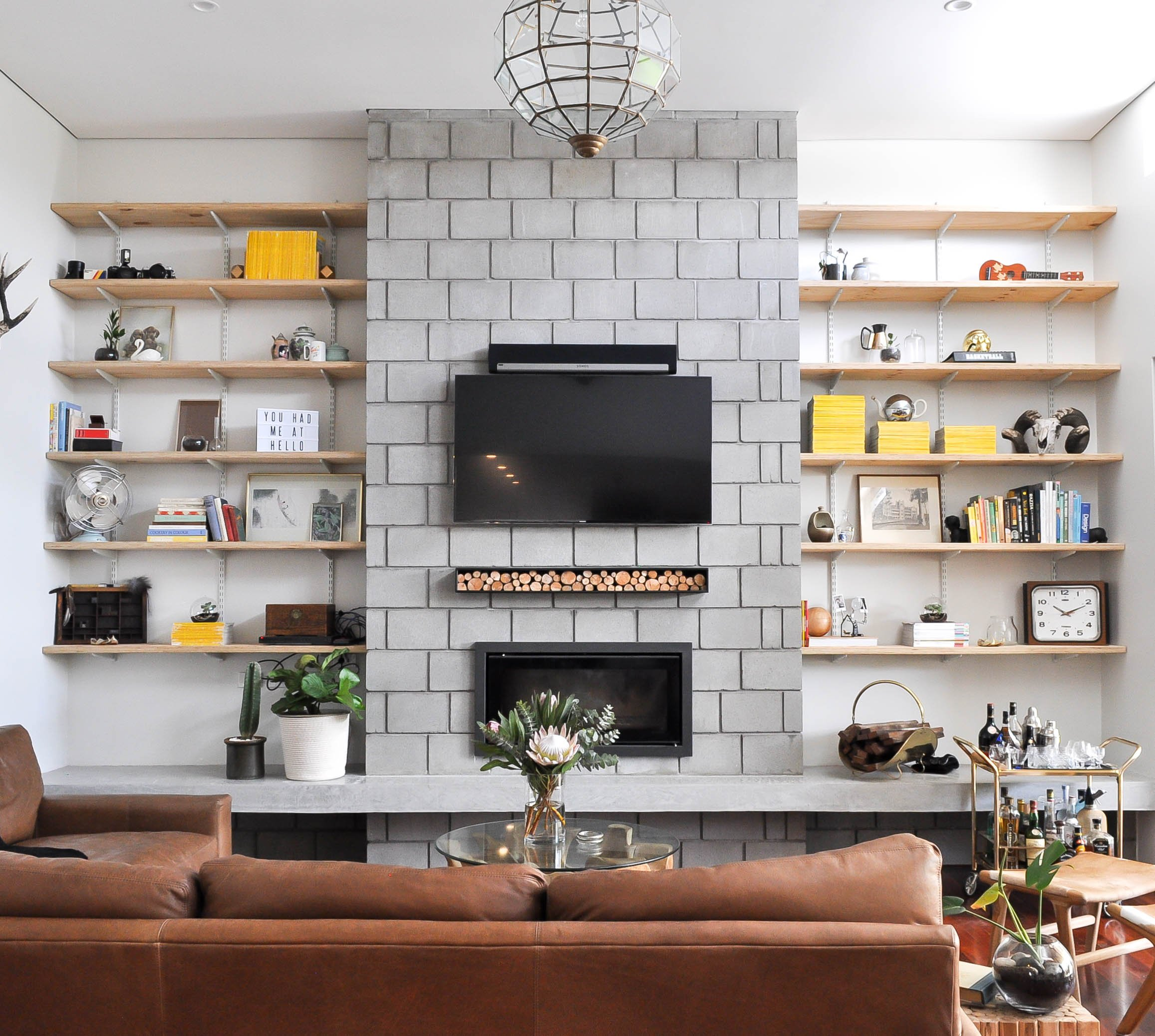 living room with open shelves and wall mount fireplace